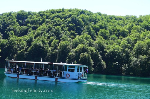 One of the boats sailing across the still waters of Plitvice